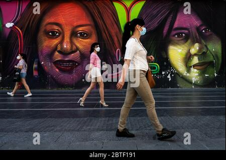Madrid, Spain. 25th May, 2020. Women wearing protective face masks maintaining social distance, walk by a mural in Gran Via street. Madrid has entered the so-called Phase One transition from the coronavirus lockdown, allowing many shops to reopen as well as restaurants to serve customers outdoors. Credit: Marcos del Mazo/Alamy Live News - Stock Photo