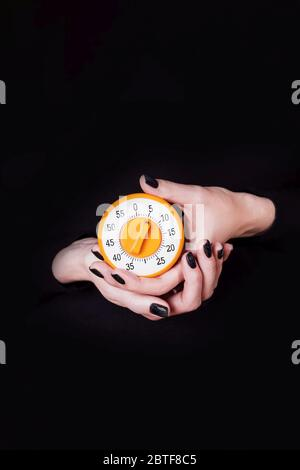 Female hands holding round orange kitchen timer on a black background. Copy space. Time concept
