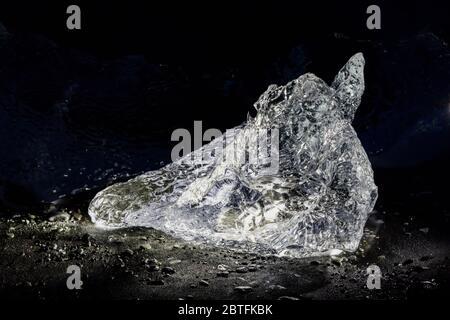 Melting chunk of clear glacial ice, originally calved into Jökulsárlón Lagoon from the Breiðamerkurjökull Glacier, at Diamond Beach on the South Coast - Stock Photo