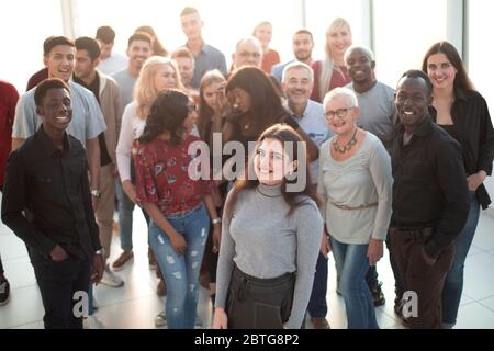 Young smiling executive standing in front of her business team - Stock Photo