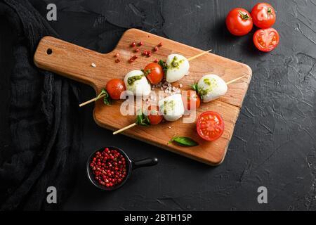 caprese salad skewer with tomato on sticks Italian traditional caprese salad ingredients. Mediterranean food. over black stone background overhead spa