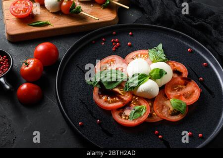 Caprese salad Tomato and mozzarella slices with basil leaves on sticks skewer and on black ceramic platwantipasta black textured background selective
