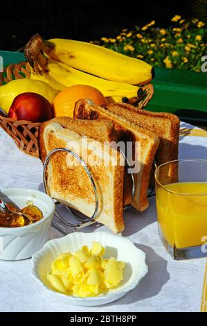 Breakfast of toast, butter, fruit, orange juice and marmalade, Costa del Sol, Andalucia, Spain, Europe. - Stock Photo