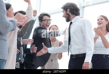 corporate group of employees congratulating each other on the victory