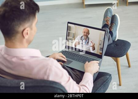 Doctor online. A man sitting in a chair has a video call helping an online mature doctor with a laptop in his apartment. - Stock Photo