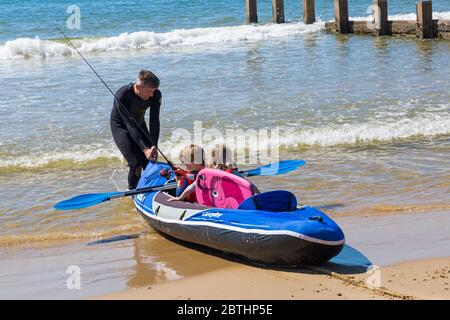 Bournemouth, Dorset UK. 26th May 2020. UK weather: another hot sunny day at Bournemouth beaches with clear blue skies and unbroken sunshine, as the glorious weather continues and temperatures rise. Sunseekers head to the seaside to enjoy the sunshine. Henry and Olivia, 6 and 5, go kayak fishing in the sea. Credit: Carolyn Jenkins/Alamy Live News - Stock Photo