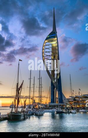 After a hot and humid day on the Hampshire coast, the lights come on at Gunwharf Quays as the sun sets over Portsmouth Harbour on the Solent and the f - Stock Photo