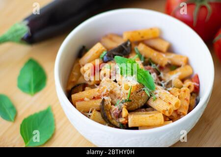Traditional Italian dish: pasta alla norma with tomatoes, eggplant, garlic, basil and ricotta cheese on a wooden cutting board - Stock Photo
