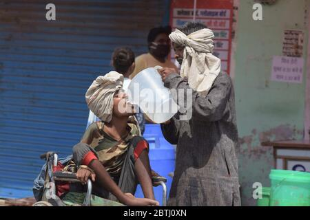 Prayagraj: A father quenching his son's thirst during a hot day amid the ongoing nationwide COVID-19 lockdown, in Prayagraj, India on May 25, 2020., Monday, May 25, 2020. (Photo by Prabhat Kumar Verma/Pacific Press/Sipa USA) - Stock Photo