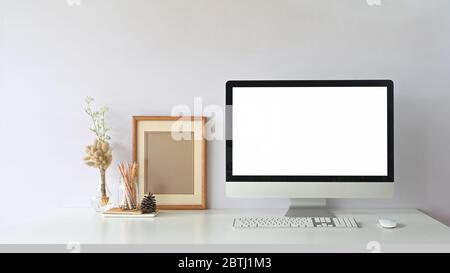 Computer monitor with white blank screen putting on workspace that surrounded by wireless mouse, keyboard, empty picture frame, pencils in glass vase - Stock Photo