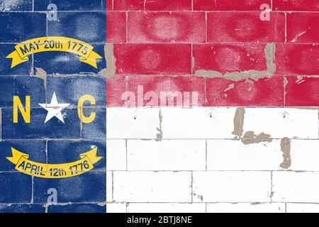 North Carolina State Flag USA Independence Day Red, Blue, and White on cracked brick wall. Political and religious disputes, customs and delivery.