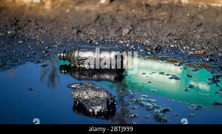 CLoseup photo of plastic bottle lying on dirty ground polluted with oil and toxic wastes. Concept of harm to environment and ecology disaster - Stock Photo