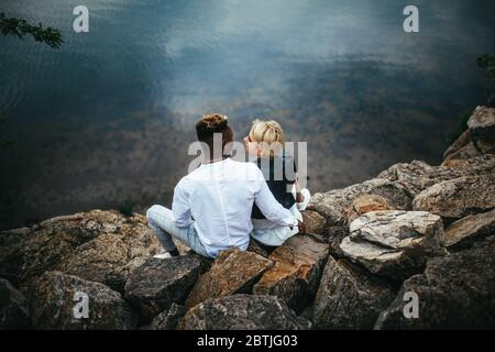 Interracial couple sits on rocks and hugs against background of river. Concept of love relationships and unity between different human races.