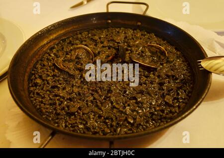 Paella is a Spanish squid ink rice dish originally from Valencia. Seafood paella from a local cafe at Barcelona. Stock Photo