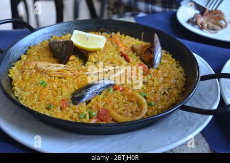 Paella is a Spanish rice dish originally from Valencia. Seafood paella from a local cafe at Barcelona. - Stock Photo