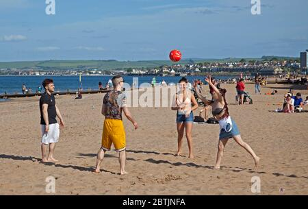 Portobello, Edinburgh, Scotland, UK. 26 May 2020. More relaxed atmosphere at the seaside late afternoon as Scotland nears the end of Phase 1 of Coronavirus Lockdown. Temperature of 19 degrees and sunny. These friends enjoy a volleyball game. - Stock Photo