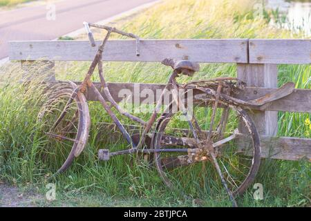 An old abandoned rusty bike parked against wooden fence. Old fashioned classic bicycle stands forgotten along a bicycle path. Fished out of the ditch - Stock Photo