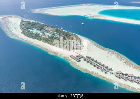 Aerial view of resort water bungalows. Luxury tropical hotel over coral reef connected with atolls in Indian ocean. Amazing travel landscape - Stock Photo