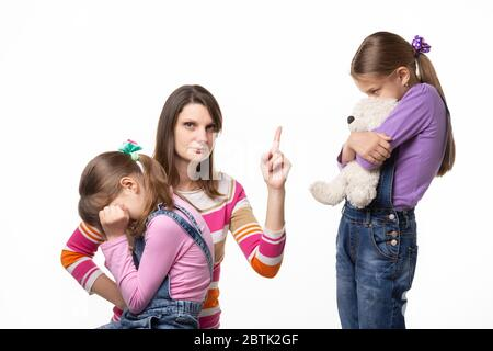 Mom talks hard with her daughter for offending her sister and looking in the frame - Stock Photo