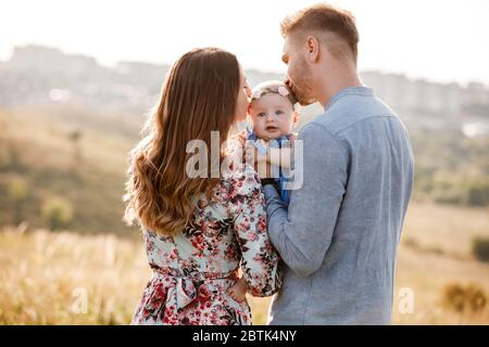 mom, dad kissing their little girl on summer day. mother's, father's and baby's day. Happy family for a walk outside the town.