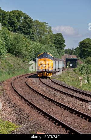 DRS Class 37 locomotive 37401 on the Cumbrian coast railway line with a Northern Rail passenger train - Stock Photo