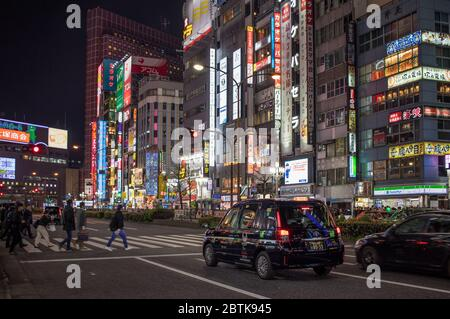 Neon streets of Kabukicho in the Shinjuku district of Tokyo at night with neon shop signs. Tokyo, Japan - Stock Photo
