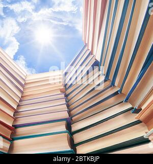 Large books pile and bright sky and sun above it. Education, science, school and study theme