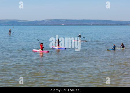 Poole, Dorset UK. 27th May 2020. UK weather: another hot sunny day at Poole beaches with clear blue skies and unbroken sunshine, as the glorious weather continues and temperatures rise. Sunseekers head to the seaside to enjoy the sunshine. Children have fun on paddleboards. Credit: Carolyn Jenkins/Alamy Live News - Stock Photo