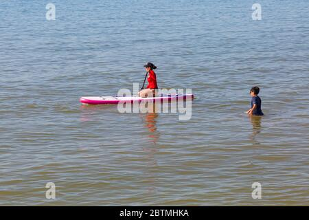 Poole, Dorset UK. 27th May 2020. UK weather: another hot sunny day at Poole beaches with clear blue skies and unbroken sunshine, as the glorious weather continues and temperatures rise. Sunseekers head to the seaside to enjoy the sunshine. Cooling down in the sea on paddleboard. Credit: Carolyn Jenkins/Alamy Live News - Stock Photo