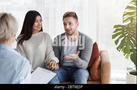 Spouses Talking With Psychologist During Appointment After Reconciliation In Office - Stock Photo