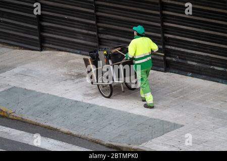 Street sweeper pushing a cart on sidewalk. Urban cleaning concept - Stock Photo