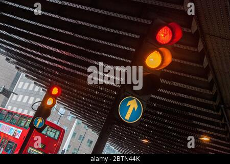 Traffic lights iluminated red and amber under a railway bridge, with a red London bus passing in the background, at London Bridge Station - Stock Photo