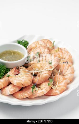 fresh boiled prawns with zesty citrus dipping sauce on white background - Stock Photo