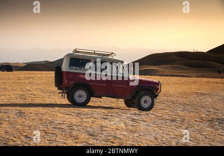 Car on the hilly terrain in sunlight. Scenic landscape of mountains. - Stock Photo