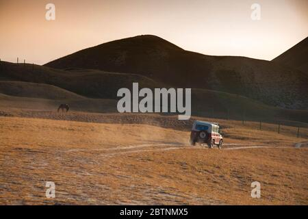 The car is driving on a sandy road in a mountainous area. The horse is grazing. Scenic landscape. - Stock Photo