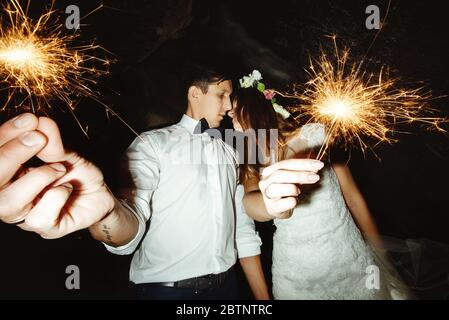 happy beautiful bride and elegant stylish groom holding fireworks on the top of a mountains in the evening - Stock Photo