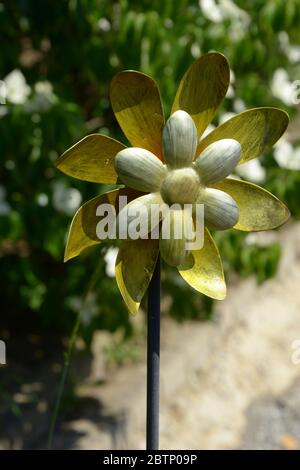 yellow-gold metalic garden windmill in a garden close-up view - Stock Photo