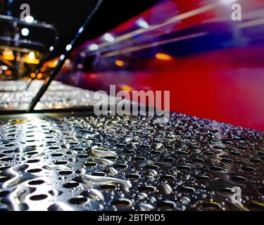 Water droplets on a bench as a train passes through Blackwall DLR Station - Stock Photo