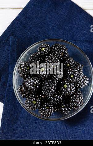 Juicy blackberry berries lie in a glass plate on a white wooden table