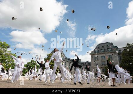 U.S. Naval Academy midshipmen toss their hats into the air at the conclusion of the commencement and commissioning ceremony for the Naval Academy Class of 2020 under COVID-19, coronavirus pandemic social distancing rules May 16, 2020 in Annapolis, Maryland. Approximately 1,000 midshipmen will graduate and be sworn-in during five events and one virtual ceremony. - Stock Photo