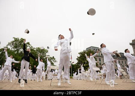 U.S. Naval Academy midshipmen toss their hats into the air at the conclusion of the commencement and commissioning ceremony for the Naval Academy Class of 2020 under COVID-19, coronavirus pandemic social distancing rules May 18, 2020 in Annapolis, Maryland. Approximately 1,000 midshipmen will graduate and be sworn-in during five events and one virtual ceremony. - Stock Photo