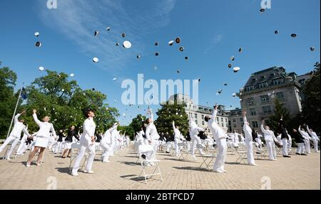 U.S. Naval Academy midshipmen toss their hats into the air at the conclusion of the commencement and commissioning ceremony for the Naval Academy Class of 2020 under COVID-19, coronavirus pandemic social distancing rules May 14, 2020 in Annapolis, Maryland. Approximately 1,000 midshipmen will graduate and be sworn-in during five events and one virtual ceremony. - Stock Photo