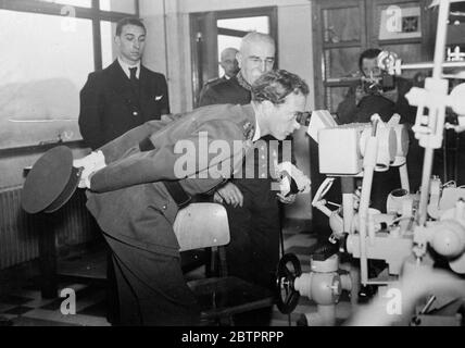 King Leopold takes a peep. King Leopold of the Belgians, bends down to look through the eye pieces of apparatus in the laboratory of the Mining School of the University of Liege when he attended the centenary celebrations. 29. November 1937 - Stock Photo