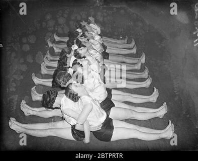 Railway girls keep fit. One Hundred girl workers of the Great Western Railway are attending regular classes in connection with the 'Keep Fit' Movement, at the Stanley Street , industry, Paddington, London. Photo shows, the ' Keep Fit' girls ran one of the exercises. 27 November 1937 - Stock Photo