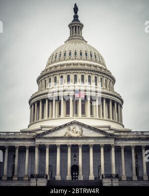The Neoclassical style dome of the United States Capitol building against a gray, moody sky in Washington, D.C.
