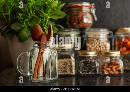 Food set. Raw cereals, pasta, groats, organic legumes and useful seeds in glass jars. Vegan source of protein and energy resources. Food storage in glass jars, eco shopping, on a dark background, Zero waste storage concept, Recycling, Sustainable lifestyle concept