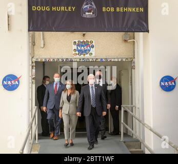 Cape Canaveral, United States of America. 27 May, 2020. U.S. Vice President Mike Pence and Karen Pence, joined by NASA Administrator Jim Bridenstine, left, and Elon Musk, SpaceX Chief Engineer, right, exit the Neil Armstrong Operations and Checkout Building to view the Demo-2 mission launch at the Kennedy Space Center May 27, 2020 Cape Canaveral, in Florida. The NASA SpaceX Demo-2 mission is the first commercial launch carrying astronauts to the International Space Station. Credit: Bill Ingalls/NASA/Alamy Live News Credit: Bill Ingalls/NASA/Alamy Live News - Stock Photo