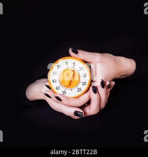 Female hands holding round orange kitchen timer on a black background. Copy space. Time concept, expectation