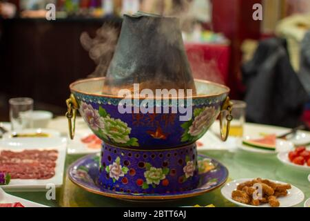 Beijing / China - December 31, 2015: Traditional Beijing style Chinese coal-heated brass hot pot placed at the center of the dining table at a restaur - Stock Photo