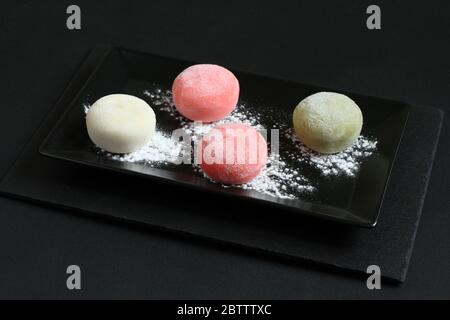 Four types of Japanese dessert mochi - pomegranate with honey, green matcha tea, strawberry, coconut on a black plate on a black table. - Stock Photo